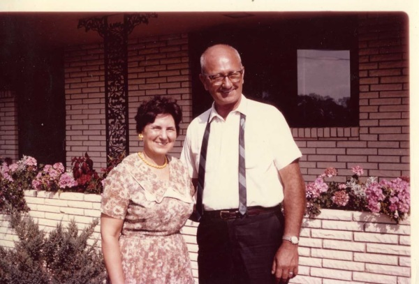 Audrey and Dale in front of new house.  Audrey loves flowers behind them that Dale had gardener plant.